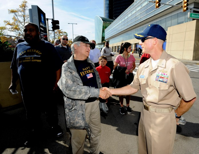 USS Detroit Commanding Officer Michael Desmond, right, greets David Boysnack, center, 61, of Dearborn Heights, and Gerard Jones, left, 51, of Detroit. Tthe commander thanked them for their service.
