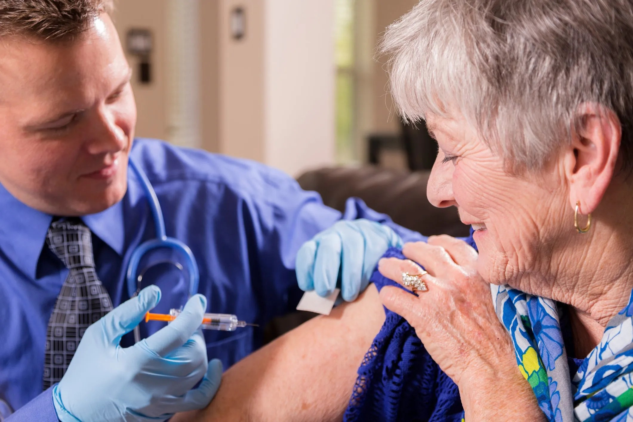 A physician administering a vaccine into the arm of an elderly woman.