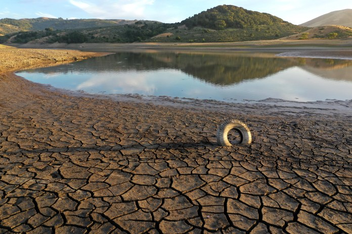 A tire is wedged between cracks in dry earth at Nicasio Reservoir in Nicasio, Calif., as the state comes under exceptional drought.