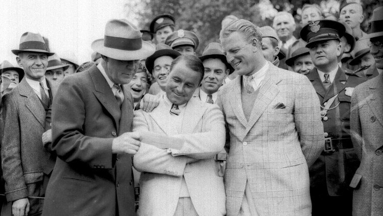 """Sarazen, center, smiles as he receives a $1,500 check for winning the Augusta National Tournament in Augusta, Ga., in this April 8, 1935 photo. Presenting the check is Grantland Rice. At right is golfer Craig Wood. Trailing Wood by three strokes with just four holes remaining, Sarazen holed a 235-yard 4-wood shot on the 15th hole for a double-eagle 2, then won in a playoff. It was """"the shot heard round the world."""""""