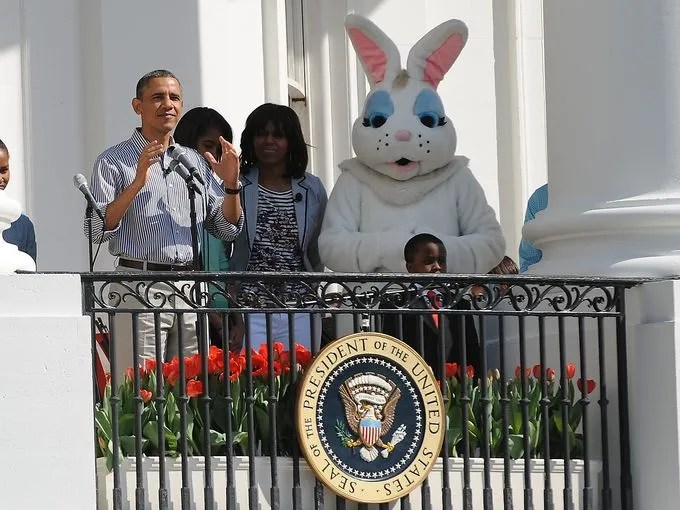 "President Obama welcomes people to the egg roll as first lady Michelle Obama, the Easter Bunny and ""Kid President"" Robbie Novak stand on the Truman Balcony at the White House."