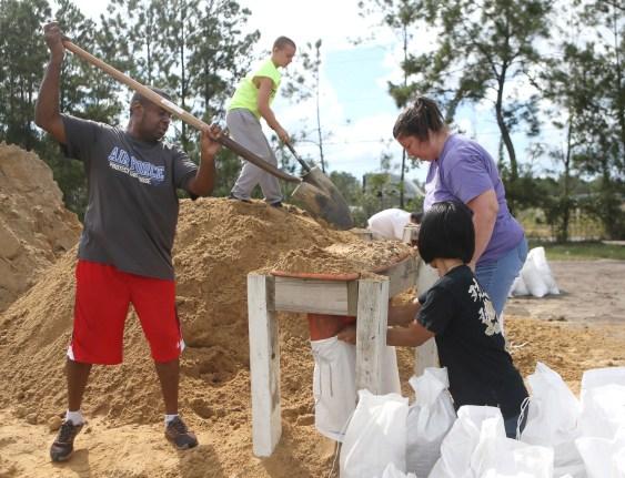 Haskel Johnson, à esquerda, com a ajuda de Daniel Tippett, Jennifer Tippett e Nobuko Johnson, à direita, enche sacos de areia no Lynn Haven Sports Complex em Lynn Haven, na Flórida, em 8 de outubro de 2018, para se preparar para o furacão Michael.
