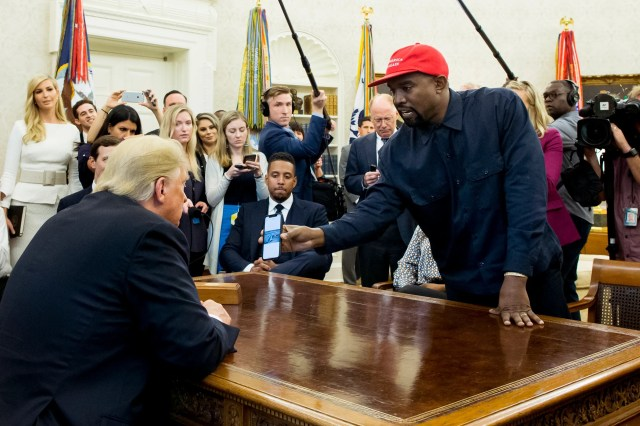 West shows a cell phone depicting the image of an aircraft to President Donald Trump during their meeting.