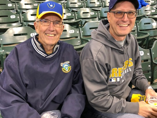 Don Kneiert (left) celebrates his 80th birthday with his son Jeff Kneiert by watching the Brewers play the Los Angeles Dodgers in the first game of the NLCS October 12, 2018.