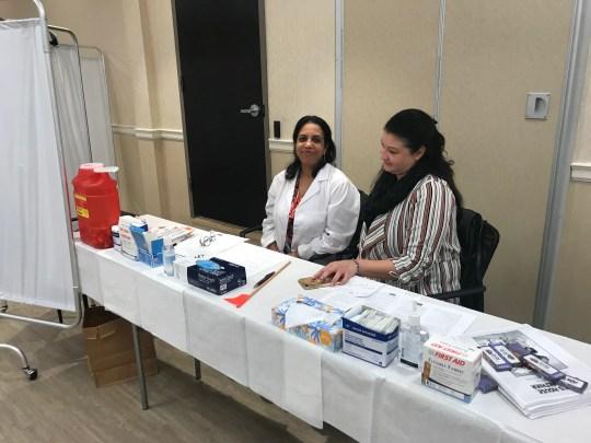 Sheela Geevarghese (l) y Xiomara Lopez con el Departamento de Salud del Condado de Rockland administran las vacunas contra el sarampión, las paperas y la rubéola (MMR) en la clínica gratuita en Monsey el jueves.