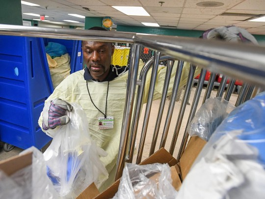 Charles Henry sorts garbage and dirty linen as part of his job in the environmental services department. Henry said he likes his co-workers and being treated with respect.