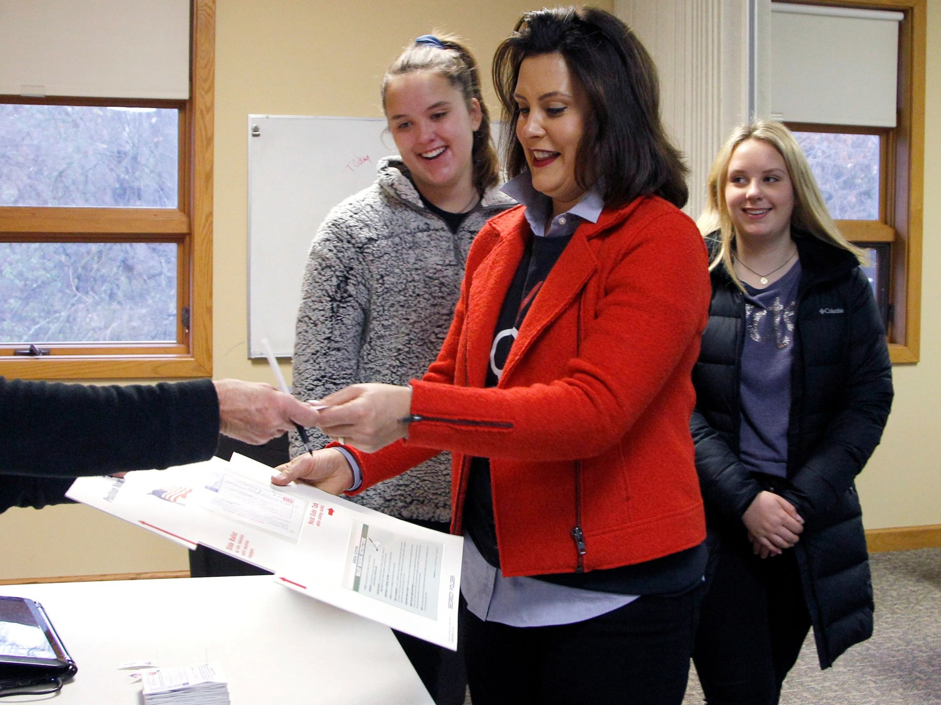 Michigan Democratic gubernatorial candidate Gretchen Whitmer, with daughters Sherry, left, and Sydney, right, turns in her privacy folder and receives a sticker after casting her ballot, Tuesday, Nov. 6, 2018, at St. Paul Lutheran Church in East Lansing.