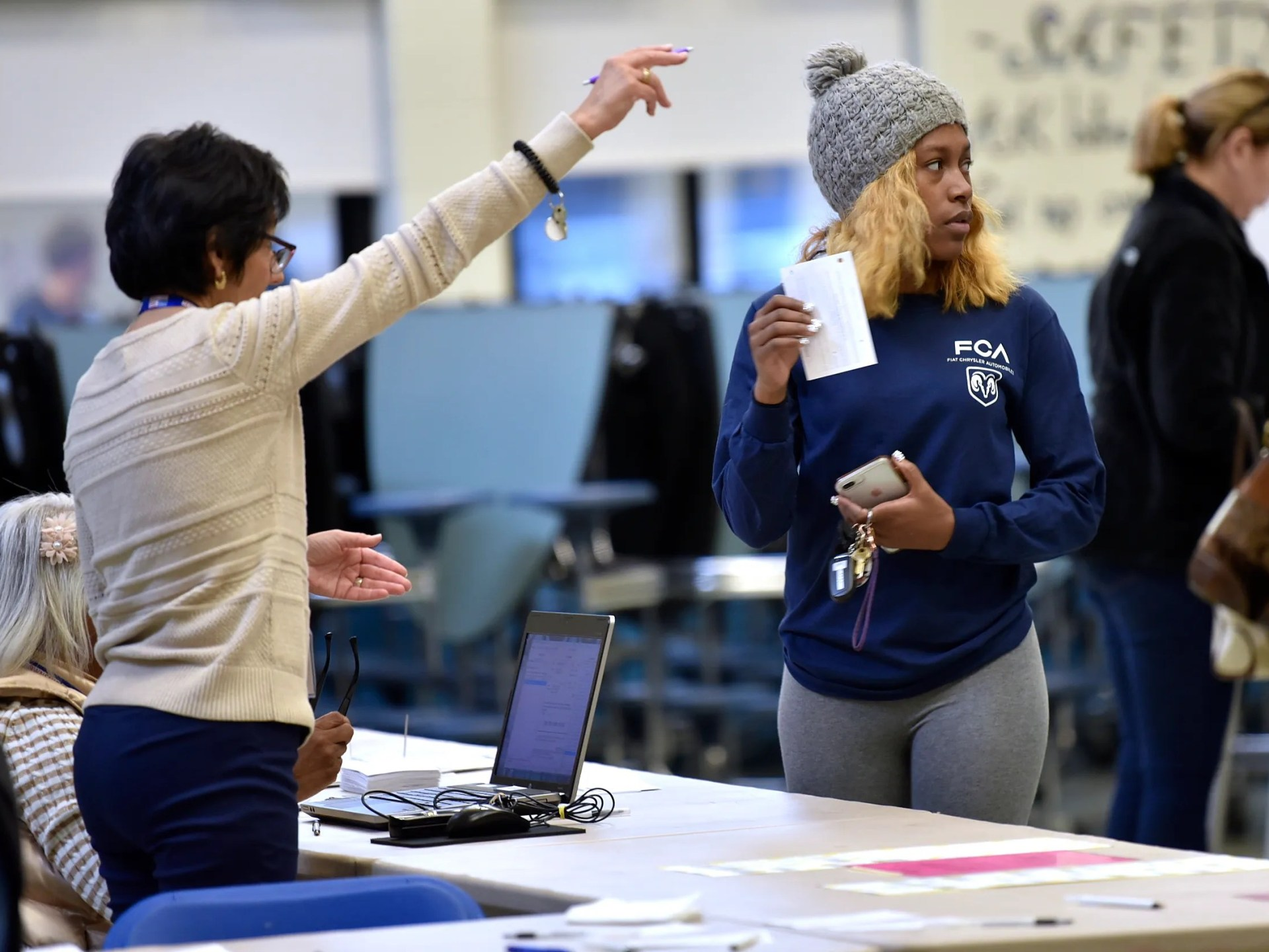 A precinct worker instructs Samara Brame, right, of Macomb Township where to get her ballot in the cafeteria at Ojibwa Elementary School. Brame is a UAW Local 140 member who builds Fiat Chrysler automobiles.