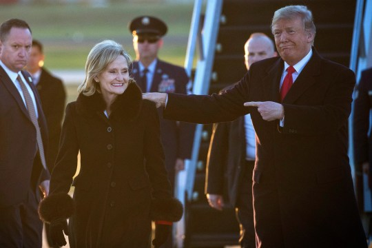 President Donald Trump points as the walks with Sen. Cindy Hyde-Smith, R-Miss., at Tupelo Regional Airport Nov. 26, 2018, in Tupelo, Mississippi.