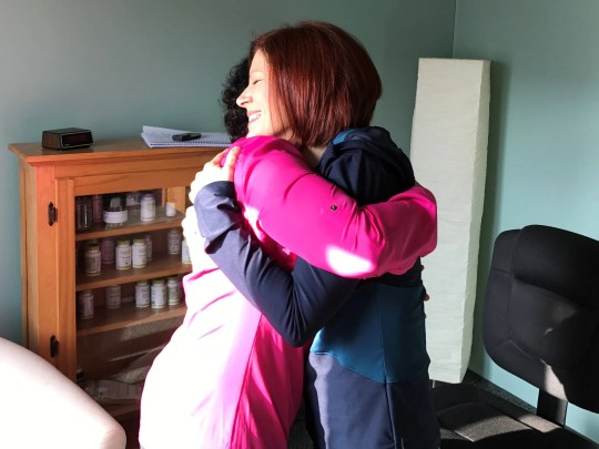 Cindy Hemingway (right) exchanges a hug with Meena Puri at the latter's Milford office. Hemingway said Puri and her ayurvedic teachings have made her a better, calmer person.