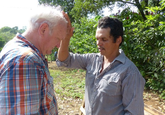 Ernesto Escoto of Los Angeles, Nicaragua, gives former Register farm editor Jerry Perkins a blessing.