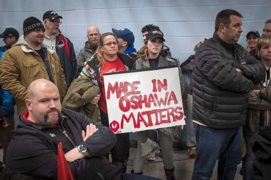 Laurie Nickel, center left, and daughter Stephanie hold a sign at a UNIFOR union meeting between workers at the General Motors plant in Oshawa with Jerry Dias, President of UNIFOR, at the Oshawa plant in Ontario, Monday, November 26, 2018.