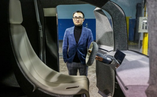 Mike Tianye Wang, Chief Executive Officer and Chairman of the Quadrobot Board stand in a warehouse where an U1 package delivery truck is located in Madison Heights, Mich. Photo on Thursday, February 5, 2019.