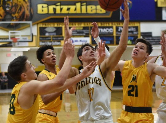 Galena's Chase Nelson is surrounded by Grizzlies he reaches for a rebound during Tuesday's game at Galena.