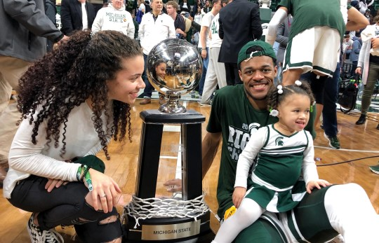 The state basketball player Xavier Tillman Michigan makes smiling on the camera while sitting with his 2 year old daughter Ayanna in her lap and her toddler Tamia Todd looking after your USU beat Michigan to reach and earned a share of her Big Ten's championship with Purdue Sunday, March 10, 2019.