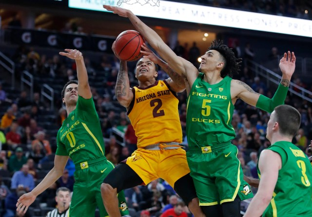 Arizona State's Rob Edwards (2) tries to shoot around Oregon's Will Richardson, left, and Oregon's Miles Norris during the first half of an NCAA college basketball game in the semifinals of the Pac-12 men's tournament Friday, March 15, 2019, in Las Vegas. (AP Photo/John Locher)