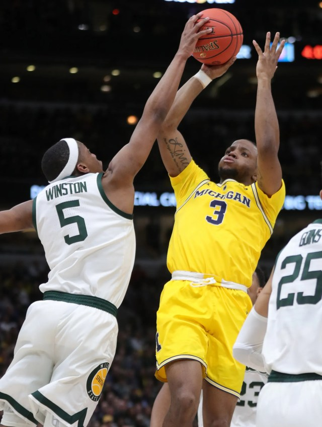 Michigan State's Cassius Winston blocks a shot by Michigan's Zavier Simpson during the first half of the Big Ten tournament championship Sunday, March 17, 2019 in Chicago.