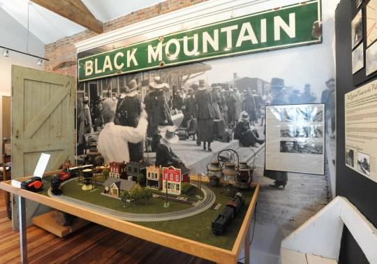 A display on the second floor gallery of the Swannanoa Valley Museum and History Center features an old metal sign that used to hang at the Black Mountain depot and an enlarged photograph of a scene from the early days of the railroad hub.