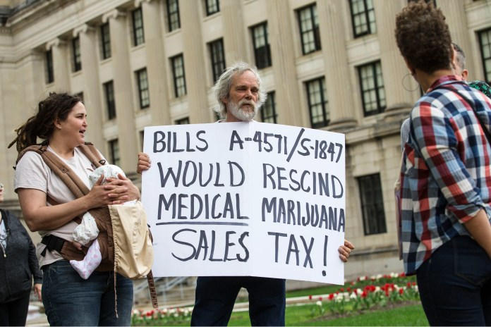 The Coalition for Medical Marijuana of New Jersey host a rally in front of the New Jersey statehouse to bring attention to marijuana legalization on the unofficial 420 holiday. Jim Miller, co-founder of CMMNJ protests about tax in front of the statehouse. 
