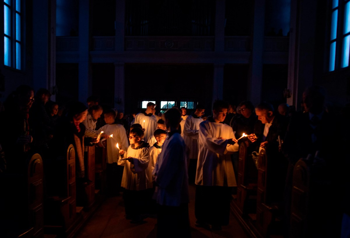 People light candles as they celebrate the Holy Saturday Easter Vigil in the catholic church of Saint Mary of Snows in Bratislava, Slovakia, on the Easter Eve on April 20, 2019.