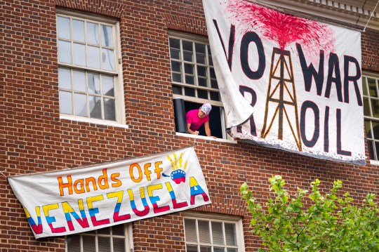 Activist Tighe Berry with the Embassy Civilian Protection Collective, which is opposed to a forced handover of diplomatic buildings belonging to the Maduro government, prepares to hang a banner as he occupies the Venezuelan Embassy in Washington, DC. The Trump administration has told the remaining diplomatic staff that they must vacate the building by the end of the day. The activists believe that representatives from the Guaido opposition will move into the Venezuelan embassy soon after.