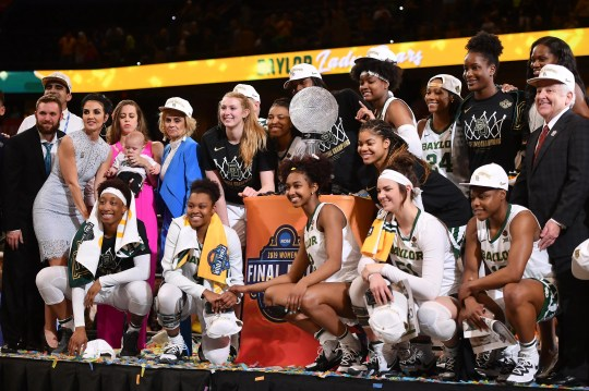 Baylor Lady Bears head coach Kim Mulkey and team pose for a photo with the coaches' trophy after defeating the Notre Dame Fighting Irish to win the championship game.
