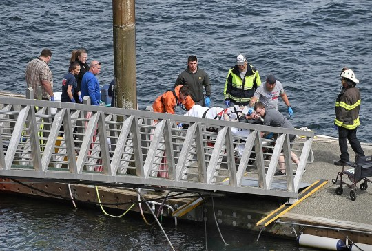 Emergency response crews transport an injured passenger to an ambulance at the George Inlet Lodge docks on Monday in Ketchikan, Alaska. The passenger was from one of two float planes reported down in George Inlet early Monday afternoon and was dropped off by a U.S. Coast Guard 45-foot response boat.