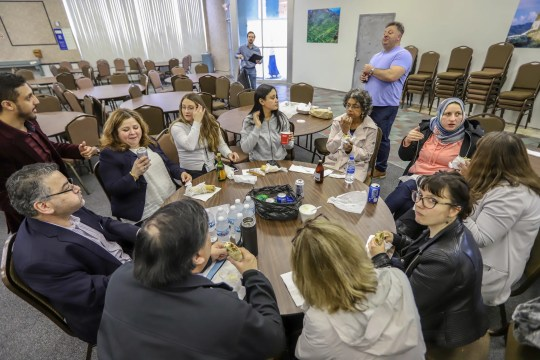 Volunteers from the International Institute of Metropolitan Detroit, Chaldean Community Foundation, South Asian American Voices of Impact, and Justice for Our Neighbors stop for lunch during the day-long Detroit New Americans campaign's citizenship workshop in Hamtramck on April 26.