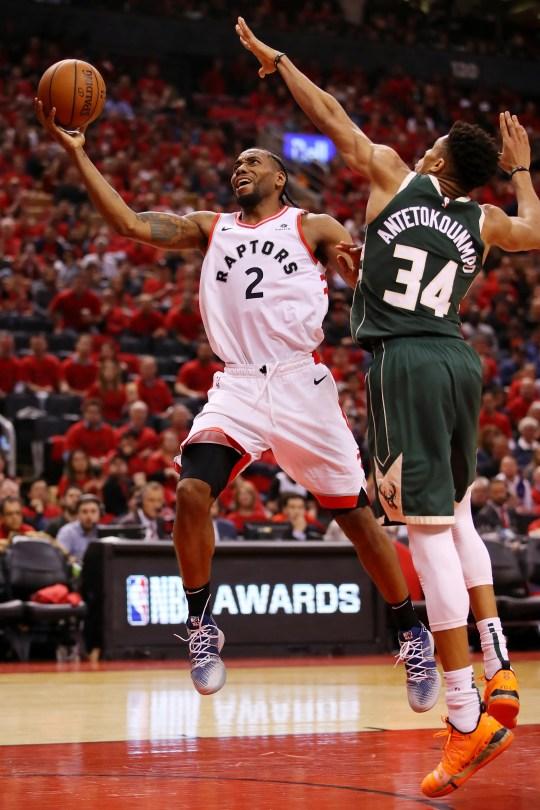 Kawhi Leonard drives to the basket against Giannis Antetokounmpo.
