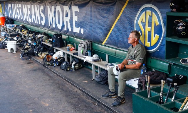 Vanderbilt coach Tim Corbin sits in the dugout watching his team celebrate their win over Mississippi after a Southeastern Conference tournament NCAA college baseball championship game, Sunday, May 26, 2019, in Hoover, Ala.