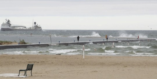 People take the northern break at Stearns Park Beach on Monday as Mississagi enters the port before the police close it because of waves hitting the wall.