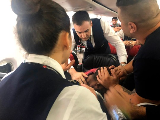 The scene as Associated Press photographer Hussein Malla observes as passengers and crew aboard a Turkish Airlines jetliner subdue a man who started screaming a few minutes after takeoff from Istanbul. Turkey, Friday June 14, 2019.