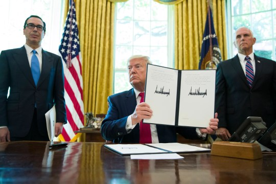 President Donald Trump holds up a signed executive order to increase sanctions on Iran, in the Oval Office of the White House, Monday, June 24, 2019, in Washington. Trump is accompanied by Treasury Secretary Steve Mnuchin, left, and Vice President Mike Pence. (AP Photo/Alex Brandon) ORG XMIT: DCAB105