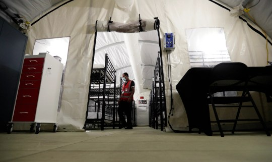 In this July 9, 2019, photo, a staff member works in the infirmary, a series of tents, at the U.S. government's newest holding center for migrant children in Carrizo Springs, Texas.