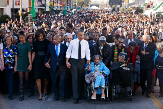 """President Barack Obama, center, walks as he holds hands with Amelia Boynton Robinson, who was beaten during """"Bloody Sunday,"""" as they and the first family and others including Rep. John Lewis, D-Ga,, left of Obama, walk across the Edmund Pettus Bridge in Selma, Ala. for the 50th anniversary of """"Bloody Sunday,"""" a landmark event of the civil rights movement, Saturday, March 7, 2015. From front left are Marian Robinson, Sasha Obama. first lady Michelle Obama. Obama, Boynton and Adelaide Sanford, also in wheelchair."""