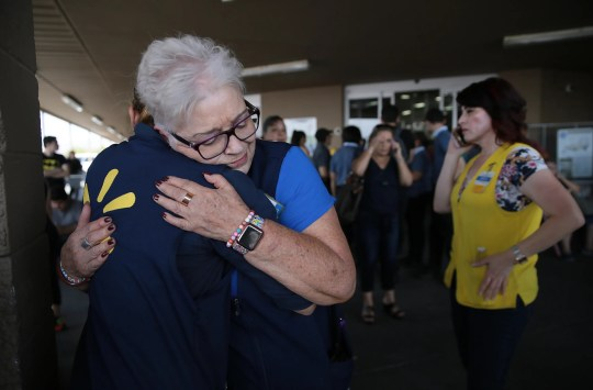 Walmart employees comfort one another after a shooter opened fire at the Walmart at Cielo Vista Mall in El Paso on Saturday, Aug. 3, 2019.
