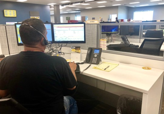 Un agente de servicio al cliente de DHL Express trabaja en su escritorio.