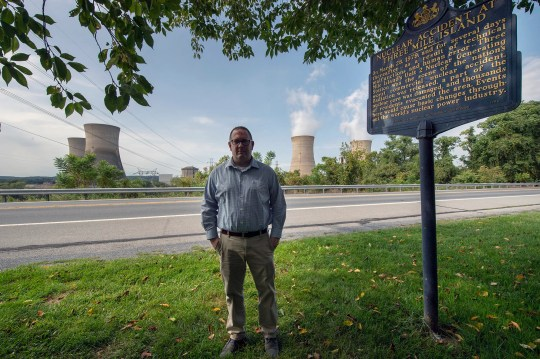 Erik Fasick stands between the view of the Three Mile Island cooling towers in front of the Exelon Generation Three Mile Island Training Center. A Pennsylvania historical plaque that explains the 1979 accident is to his right.