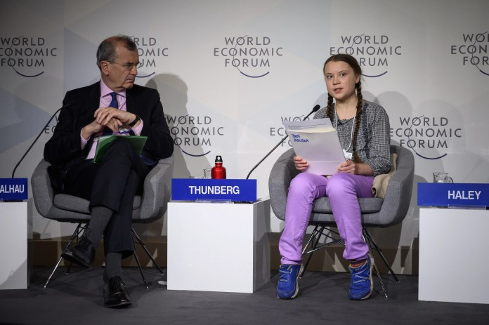 Greta Thunberg delivers a speech next to Governor of the Bank of France Francois Villeroy de Galhau during the closing day of the World Economic Forum annual meeting, on January 25, 2019 in Davos, Switzerland.