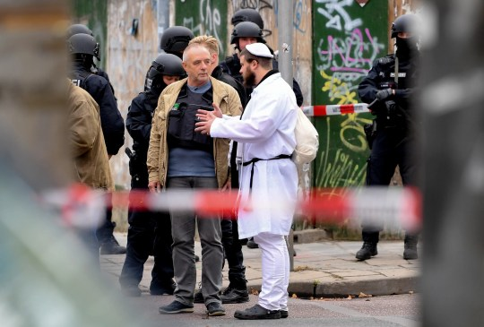 A synagogue visitor talks to police after a shooting at a synagogue in Halle, Germany, October 9, 2019. According to the police two people were killed in shootings in front of a Synagogue and a Kebab shop in the Paulus district of Halle in the East German federal state of Saxony-Anhalt. Police stated a suspect is already in arrest. Media report the mayor of Halle speaks of an amok situation.
