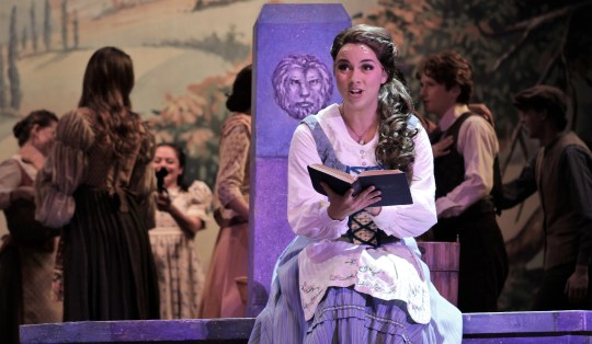 "Belle (Lauren McDonald) enjoys a good book on the town square in this rehearsal scene from Abilene Christian University's ""Beauty and the Beast,"" which will be performed Friday and Saturday evenings and Sunday afternoon at the Abilene Convention Center. Oct. 14 2019"