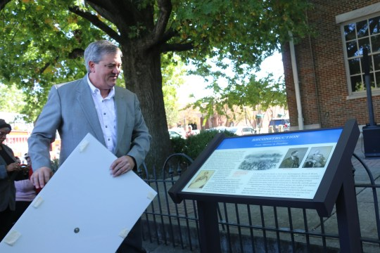 Pastor Kevin Riggs unveils a marker about reconstruction in front of the historic courthouse on Oct. 17, 2019.