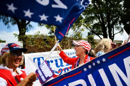Supporters of President Donald Trump gather at Benedict College as protesters demonstrate behind them Friday, Oct. 25, 2019.
