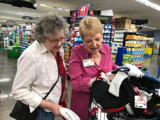 Marge Bowsher (left) and Carol Becker sift through Christmas stockings during a shopping trip. Becker volunteers for Duet, which matches people with those who need help living independently.