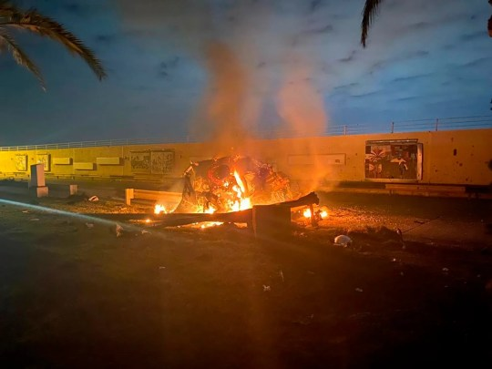 This photo released by the Iraqi Prime Minister Press Office shows a burning vehicle at the Baghdad International Airport following an airstrike in Baghdad, Iraq, early, Jan. 3, 2020.