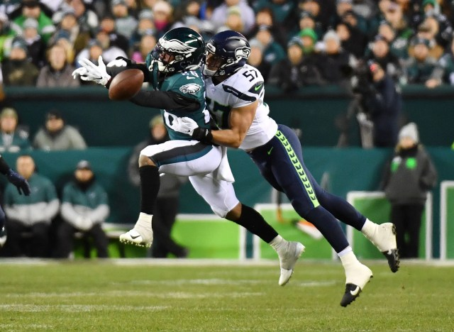 Eagles running back Miles Sanders is unable to make the catch as Seattle Seahawks linebacker Cody Barton defends.
