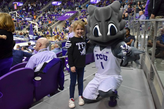 Jan. 4: TCU Horned Frogs mascot Super Frog takes a photo with a fan during the second half at Ed and Rae Schollmaier Arena.