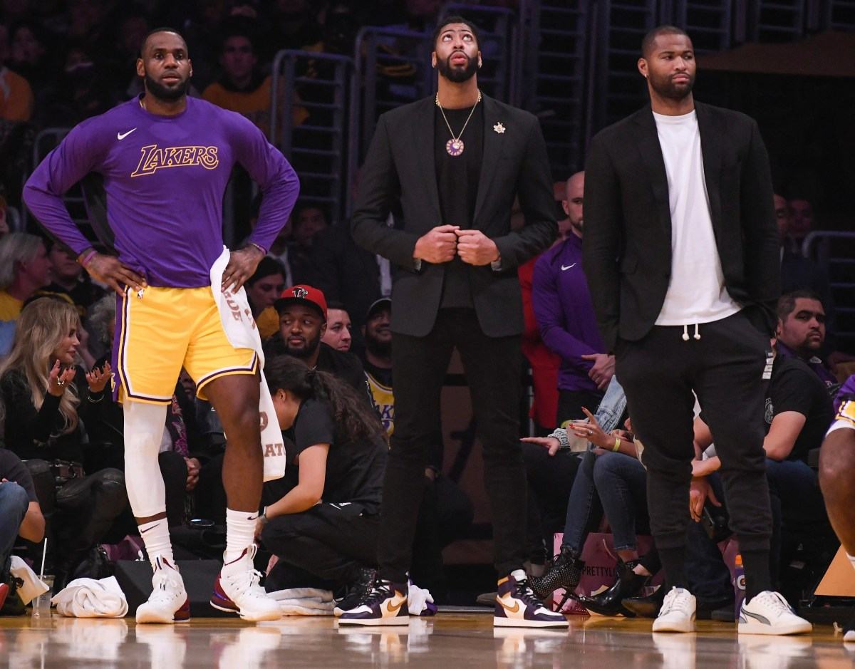 LeBron James of the Lakers, left, Anthony Davis, center, and DeMarcus Cousins, right, watch the action during Monday's game against the Cleveland Cavaliers.