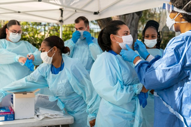 A medical team prepares to test people for COVID-19 at a drive through station set up in the parking lot of FoundCare, federally qualified health center in West Palm Beach, Fla. on March, 16, 2020.