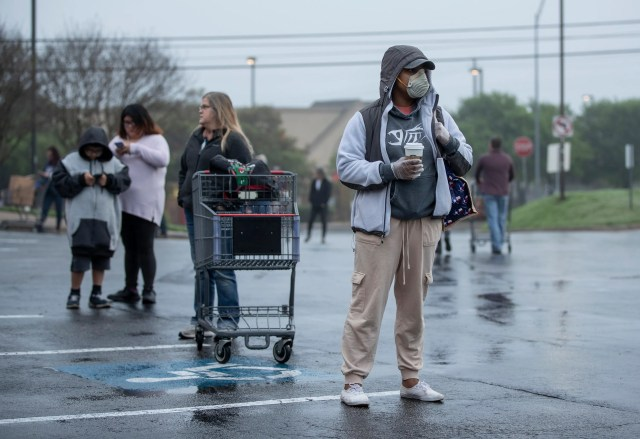 Shakaira Brooks and scores of other people wait in line with appropriate social distancing for the 8 a.m. opening of the H-E-B in the Tanglewood Village Shopping Center in South Austin on Sunday March 22, 2020, amid the coronavirus pandemic.